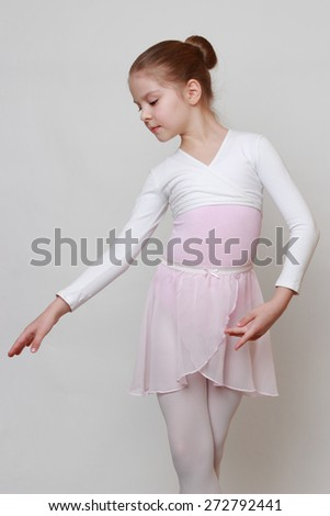 little ballerina in studio posing on camera - stock photo