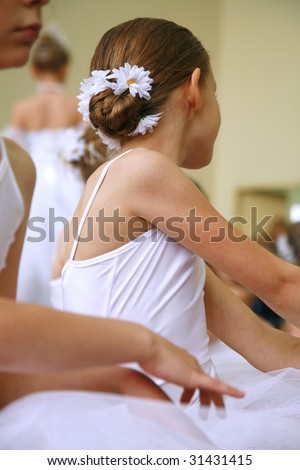 Little ballerinas dancing on a school show. Schoolgirls dressed in white dresses ( tutu ) with a daisy in their hair. - stock photo