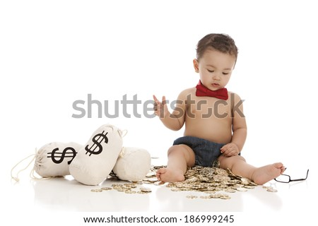 Little Banker.  Adorable baby boy wearing a red bow-tie and siting on a bunch of toy gold coins.  Isolated on white with room for your text.