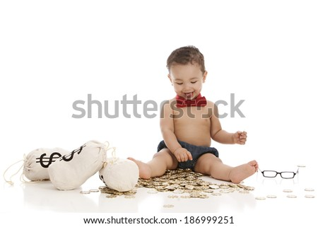 Little Banker.  Adorable baby boy wearing a red bow-tie and siting on a bunch of toy gold coins.  Isolated on white with room for your text. - stock photo