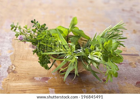 Little basket of  aromatic herbs  on old wooden plank background - stock photo