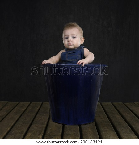 little bay boy in a terracotta flowerpot on black - stock photo