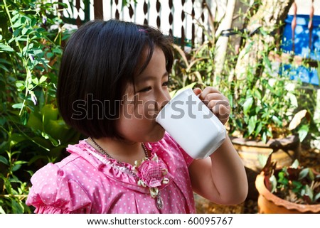 Little beautiful Asian girl drink milk - stock photo