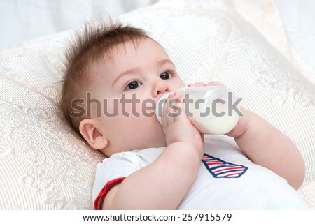 Little beautiful baby laying while holding bottle with food and eating
