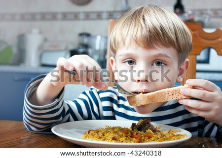 little beautiful blond boy eating at the kitchen - stock photo