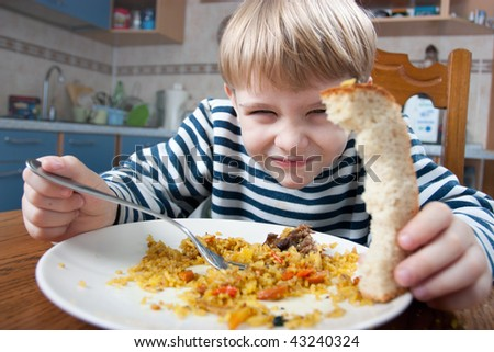 little beautiful blond boy eating at the kitchen