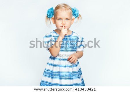 Little beautiful blond girl on a white background making shh - stock photo