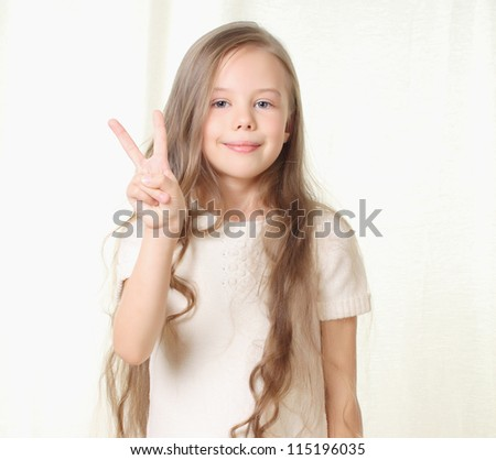 Little beautiful blond girl shows sign victory and smile - stock photo