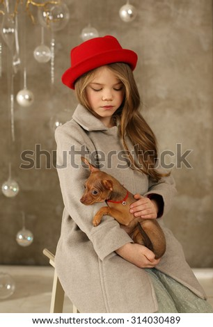 Little beautiful blonde girl in red hat with a cute puppy. Studio shot    - stock photo