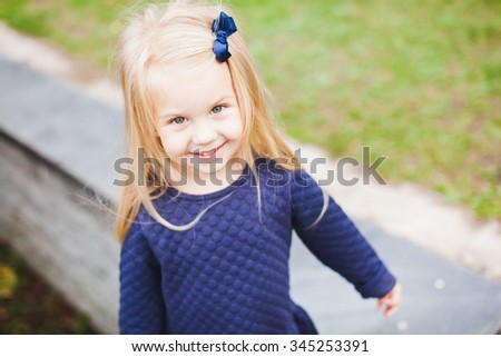 Little beautiful blonde girl with small blue bow in her hair wearing blue dress in park during walk on sunny summer autumn day. Young beautiful kid smiling and posing. Copy space - stock photo