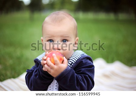 little beautiful boy eating a peach in summer park - stock photo