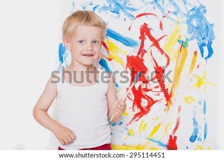 Little beautiful boy paints a picture. School. Preschool. Education. Creativity. Studio portrait over white background - stock photo