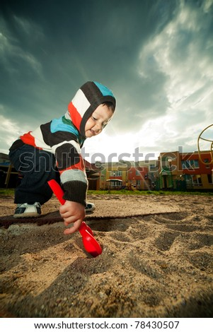 little beautiful boy plays in sandbox - stock photo