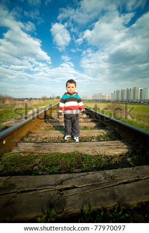 little beautiful boy plays on railroad - stock photo