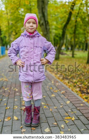 Little beautiful calm girl in a pink jacket on a background of the autumn city park. - stock photo