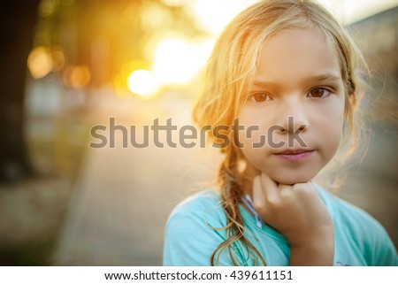 Little beautiful calm girl on a background of a sunset on a city street.