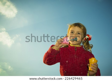 Little beautiful caucasian child girl blowing soap bubbles outdoor  at sunset, happy carefree childhood. Bright blue sky on the background. - stock photo