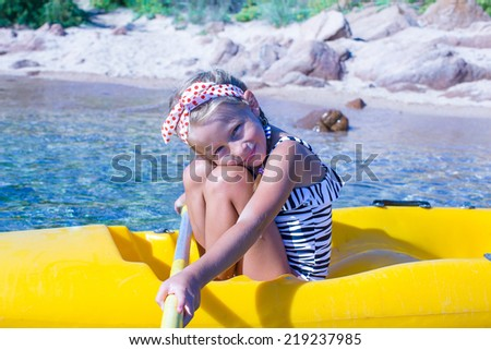 Little beautiful cute girl kayaking in the clear blue sea