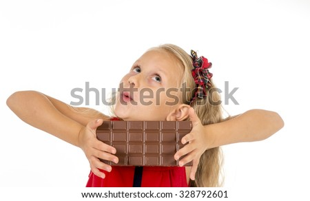 little beautiful female child in red dress holding happy delicious chocolate bar in her hands eating delighted in children sugar and sweet addiction isolated on white background - stock photo