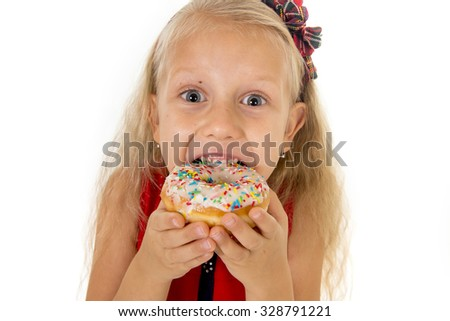 little beautiful female child with long blonde hair and red dress eating sugar donut with toppings delighted and happy isolated on white background in children sweet and sugary nutrition - stock photo
