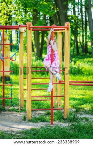 Little beautiful girl climbs on horizontal bar at playground in summer city park.