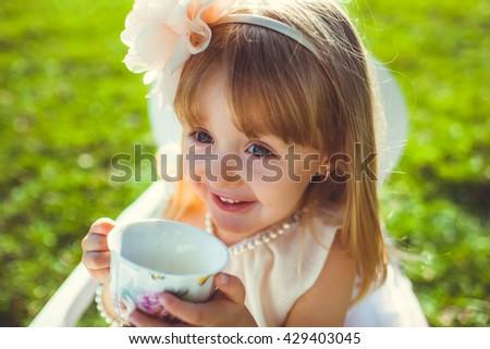 Little beautiful girl drinking tea - stock photo