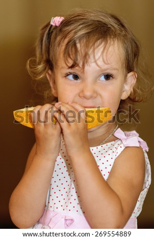 Little beautiful girl eating yellow melon. - stock photo
