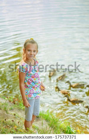 Little beautiful girl feeding ducks at pond in summer city park. - stock photo