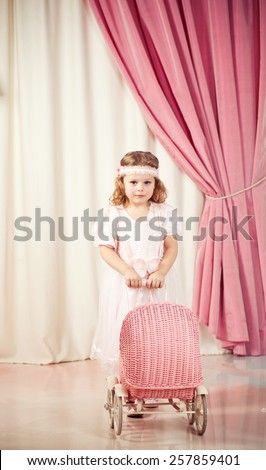 Little beautiful girl game with pram - stock photo