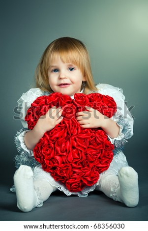 little beautiful girl holds big red heart - stock photo