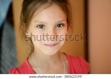 Little beautiful girl in a red blouse close-up in a large room.