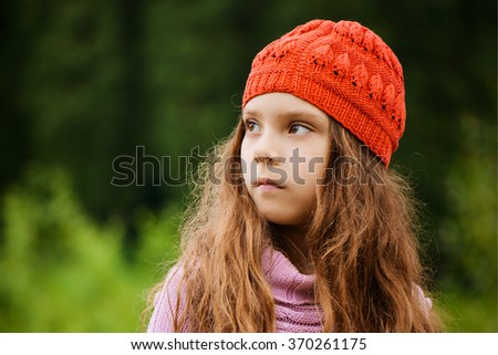 Little beautiful girl in a red cap and pink sweater on a background of green park.