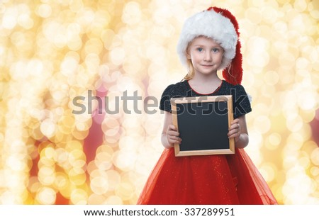 Little beautiful girl in a Santa Claus hat. Insert tex. Blackboard for text. New Year's holidays. Young girl celebrates Christmas - stock photo