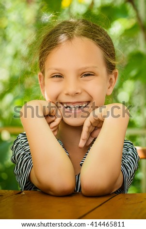 Little beautiful girl in a striped blouse close-up of a wooden table in the summer plot. - stock photo