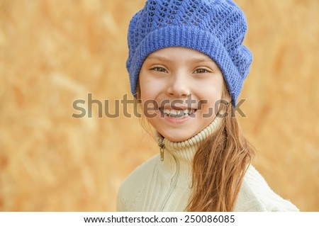 Little beautiful girl in blue beret laughing, against the background of wall from MDF. - stock photo