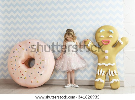 Little beautiful girl in elegant pink  dress and huge donut and , standing. Birthday party. Indoor - stock photo