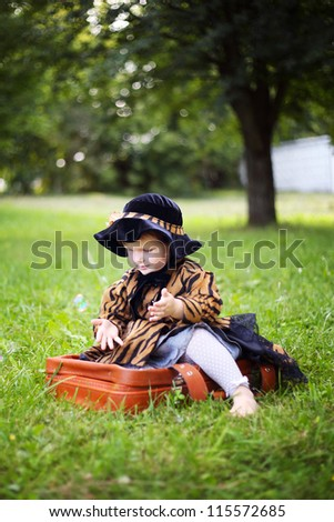 little beautiful girl in hat and cloak  sitting on suitcase in autumn park