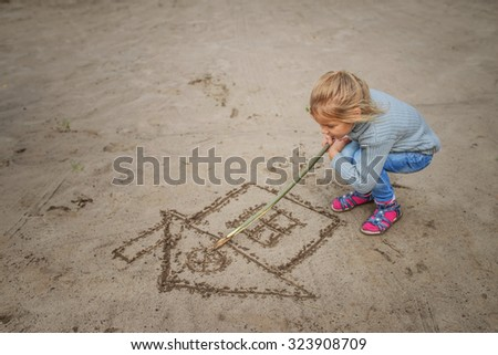 Little beautiful girl in hood draws in sand image of house. - stock photo