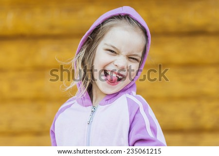 Little beautiful girl in hood poses faces and shows tongue. - stock photo