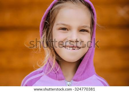 Little beautiful girl in jacket with hood and hamming builds grimaces. - stock photo