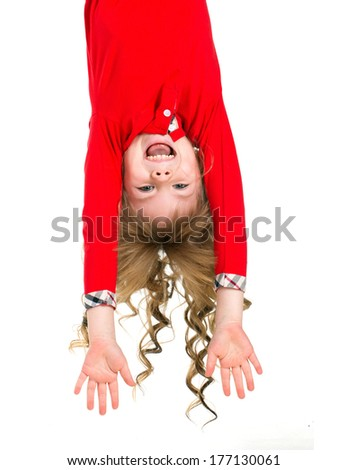 Little beautiful girl in red clothes with long blond curls hanging upside down isolated on white - stock photo