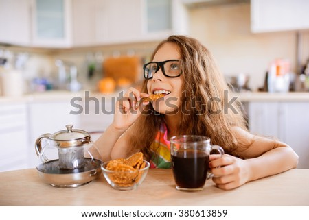 Little beautiful girl in sunglasses drink tea and eat cookies at the kitchen table. - stock photo