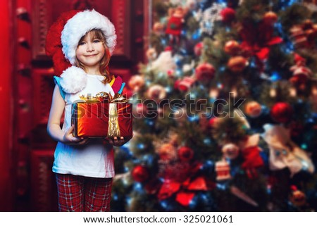 Little beautiful girl in the hat of Santa Claus and gift in the hands stands near a Christmas tree. Celebrating Christmas. New Year's holidays. Christmas gift under the tree - stock photo