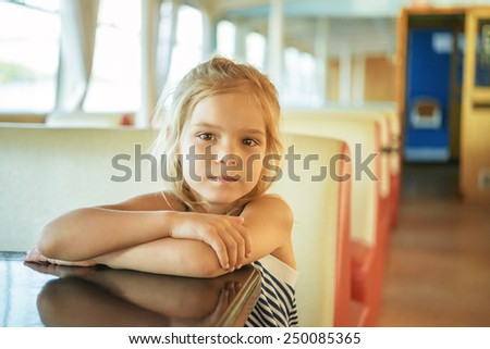 Little beautiful girl is sitting on bottom of boat-trip. - stock photo