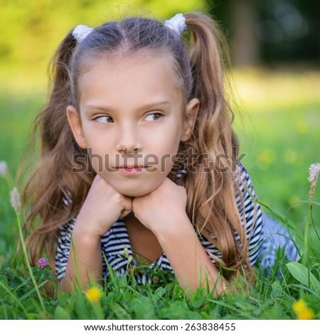 Little beautiful girl lies on green grass, summer in city park. - stock photo