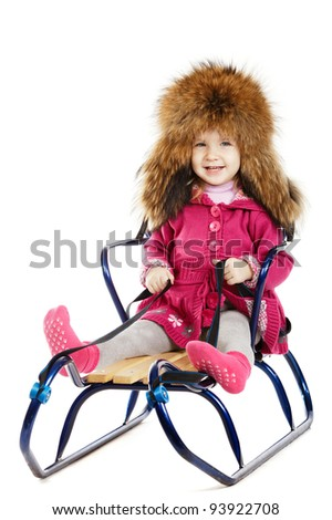 little beautiful girl on a sled isolated - stock photo