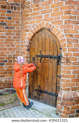 Little beautiful girl opens Wooden massive door in an ancient fortress Europe. - stock photo