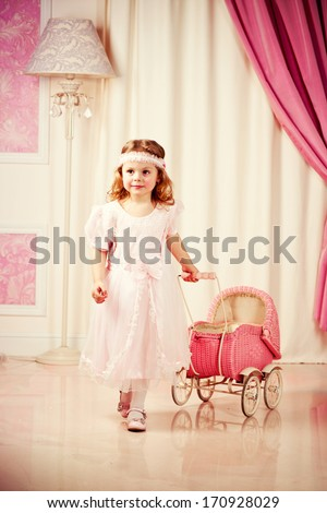 Little beautiful girl play with pram - stock photo