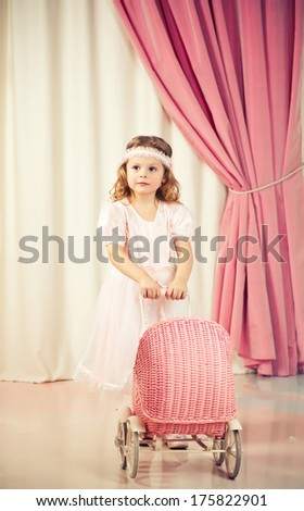 Little beautiful girl play with pram - stock photo