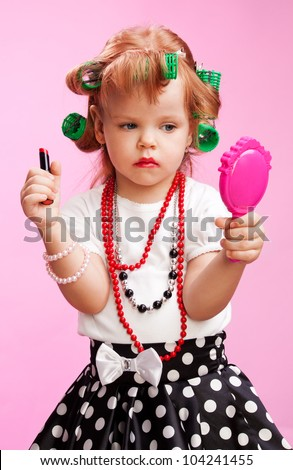Little beautiful girl playing to be a big sister, with using  lipstick, mirror, rollers and others